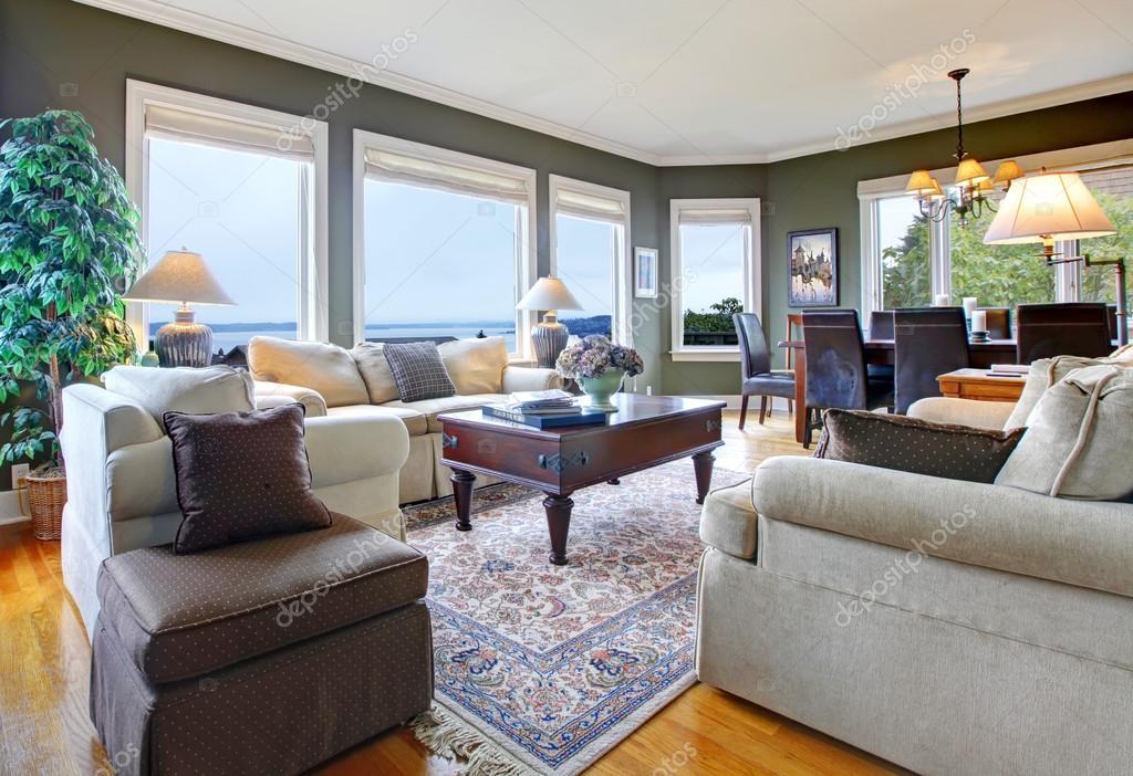 klassiska gröna vardagsrum med fina möbler och många fönster ...