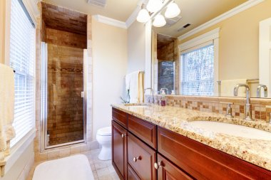 Large bathroom with cherry cabinets and granite countertop.