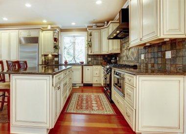 Large luxury white kitchen with cherry hardwood.