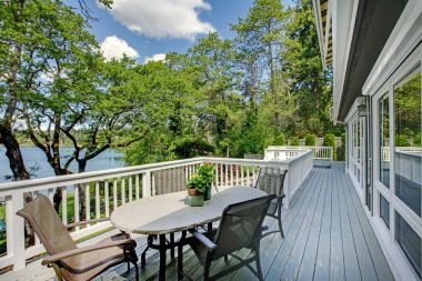 Large long balcony home exterior with table and chairs, lake view.