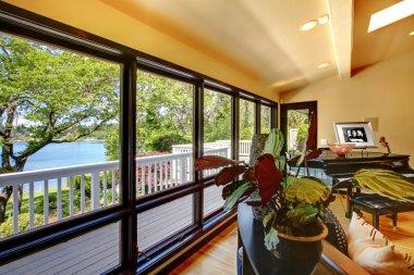Open modern luxury home interior living room wth balcony window wall.
