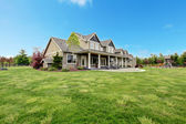 Tavaszi zöld táj nagy farm vidéki ház.