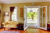 Fotografie Wohnzimmer mit offenen Türen zur Veranda. Romantischer Klassiker.
