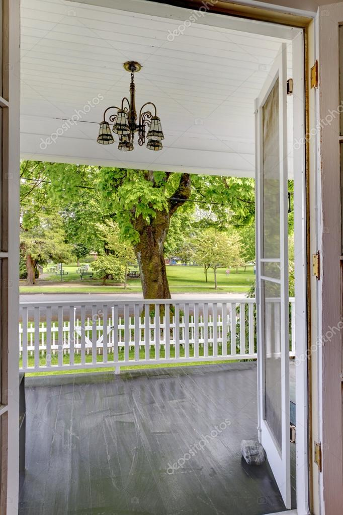 Open door to the front porch with view of the park.