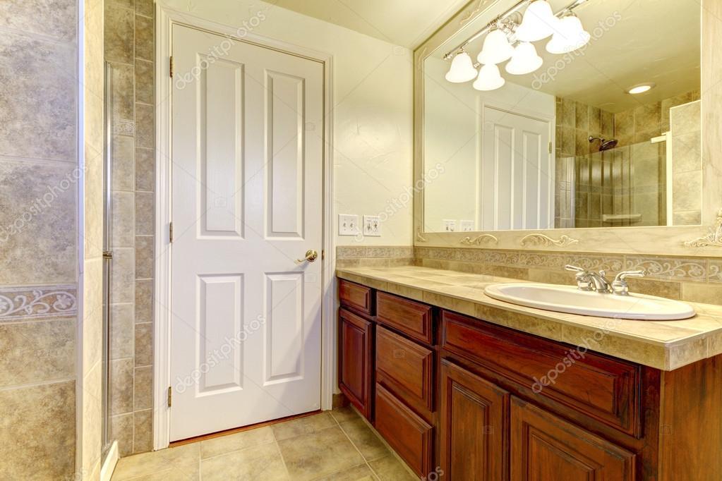 Badkamer met stenen tegels en douche met houten kasten u stockfoto