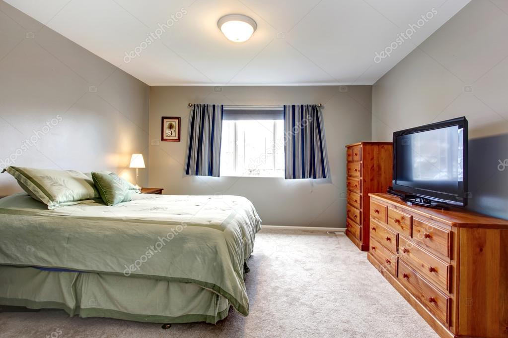Grote grijze slaapkamer met dressoir tv en blauw gordijnen