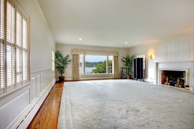 Large empty living room with fireplace and lake view.