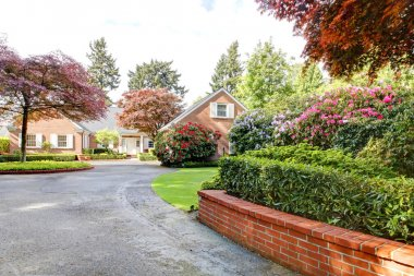 Brick red house with English garden and white window shutters and driveway.
