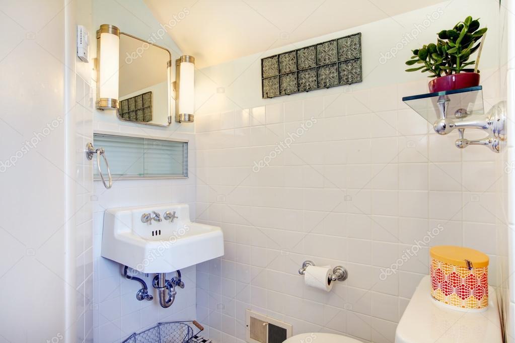 Witte badkamer versierd met bloempot en rustieke hanger