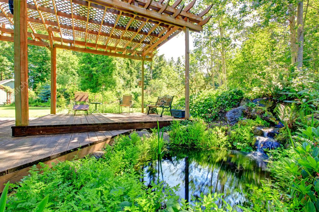 Picturesque backyard farm garden with small pond and patio area