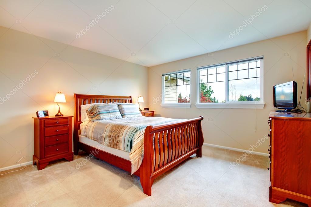 Warme kleuren slaapkamer met houten meubilair u stockfoto