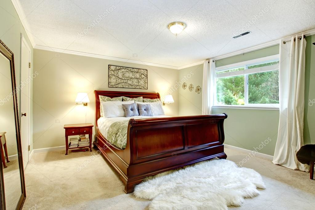Bright Bedroom With Light Mint Wall, Beige Carpet Floor, White Soft Rug.  Furnished With Cherry Carved Wood Bed And Nightstand U2014 Photo By Iriana88w