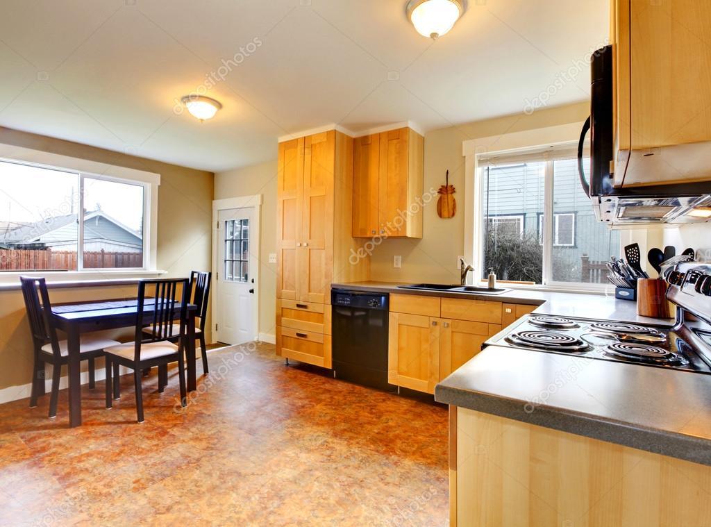 cocina y mesa de comedor con las paredes verdes y gabinetes de arce ...