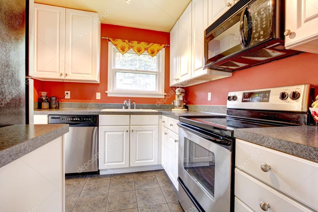 camera accogliente cucina con parete rossa e bianche armadi — Foto ...