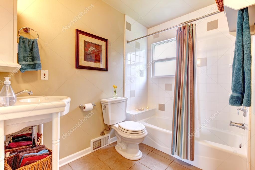 Helles Weißes Und Elfenbein Badezimmer Mit Beige Fliese Boden. Weiße Wanne  Mit Gestreiften Vorhängen Dekoriert U2014 Foto Von Iriana88w