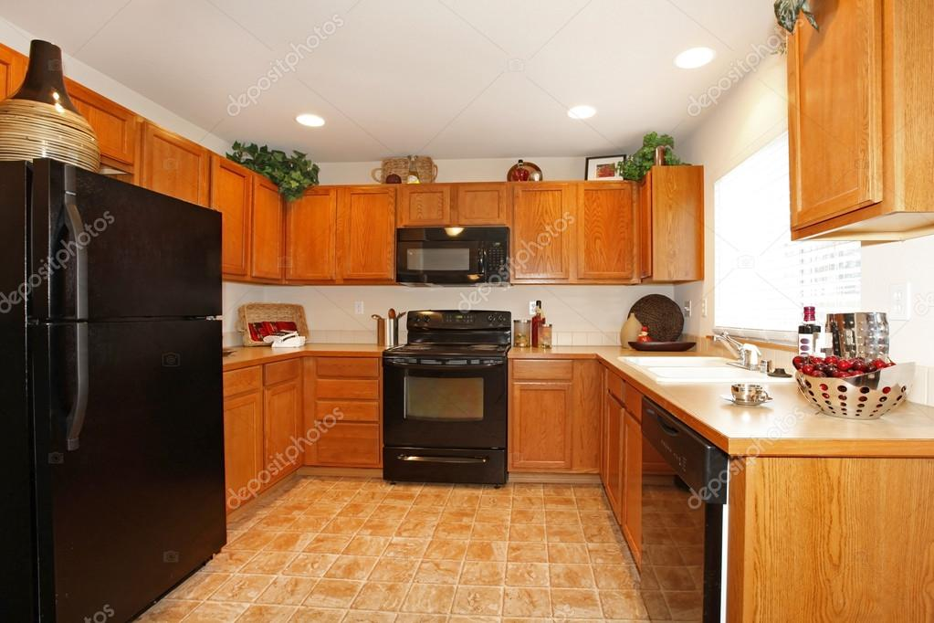 marrón gabinetes de cocina con electrodomésticos negros — Fotos de ...