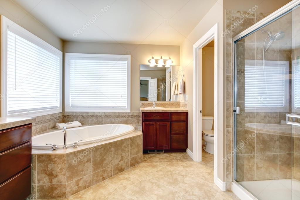 Beige Badezimmer Mit Windows Und Kirsche Hölzerne Schränke, Glas Tür Dusche.  Ansicht Der Runde Weiße Badewanne U2014 Foto Von Iriana88w