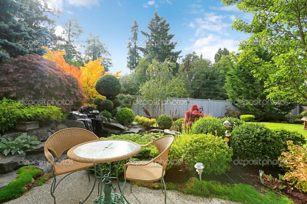 Casa Jardin Tropical Con Juego De Mesa De Mimbre Fotos De Stock