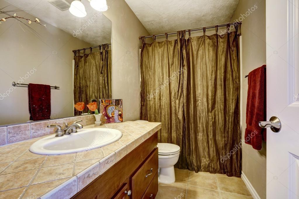 badkamer met bruin kabinet en mosterd gordijnen — Stockfoto ...
