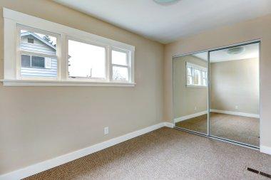 Bright empty bedroom with mirror door closet