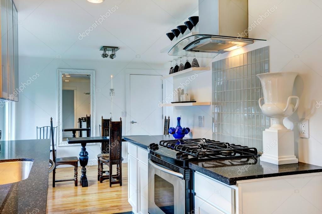 interior de cocina con encimeras de granito negro y mesa de madera ...