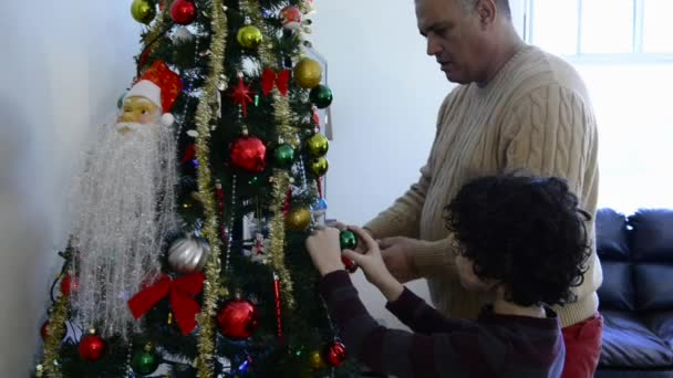 Small Latin family decorating the Christmas tree