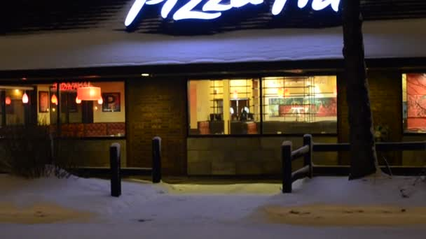 Pizza hut úložiště v noci ve městě, zatímco snowfalling