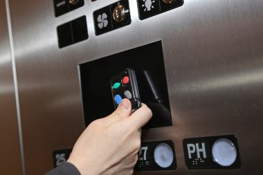Woman tapping key fob inside elevator