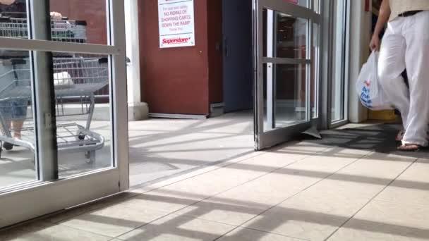lidé s nákupní košík procházel dveřmi supermarket