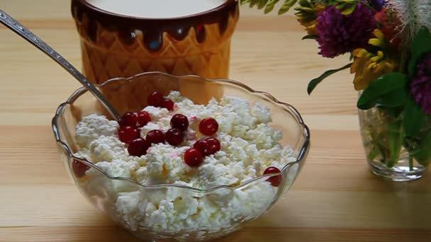Berry brusinky smíchané s lžící s tvarohem v misce