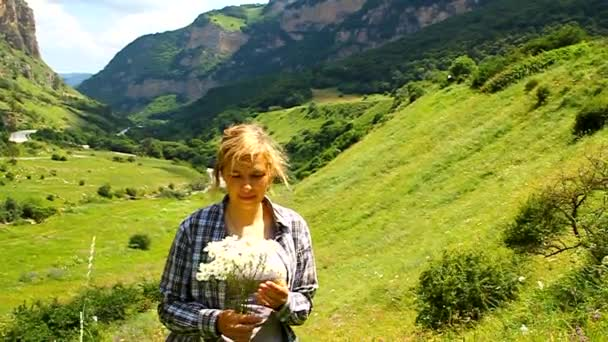 Happy woman with a bouquet of daisies in a meadow in the mountains