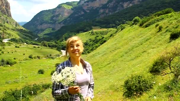 Happy woman walking with a bouquet of daisies in a meadow among the mountains