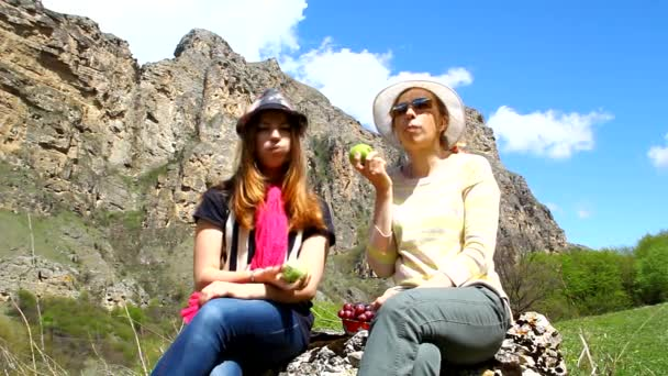 Happy family mother and daughter sitting on a rock and eating fruits outdoors in the mountains