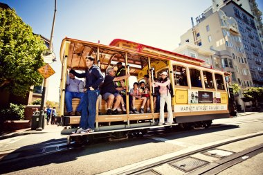 Passengers enjoy a ride in a cable car in San Francisco