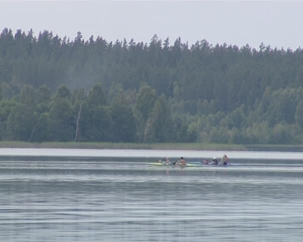 Kanus rasen schnell in einen See, gefilmt vom Seeufer.
