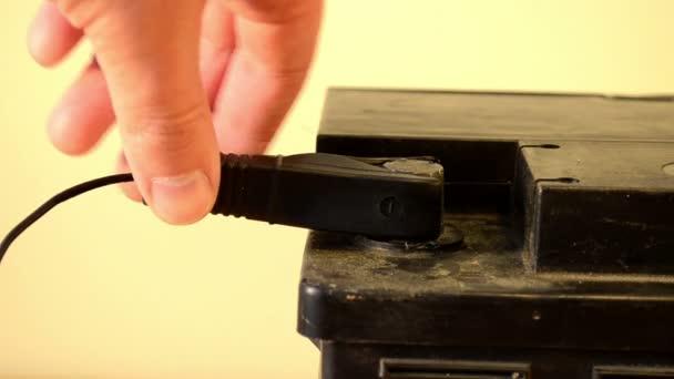 closeup hand unplug car battery charger black clamp accumulator