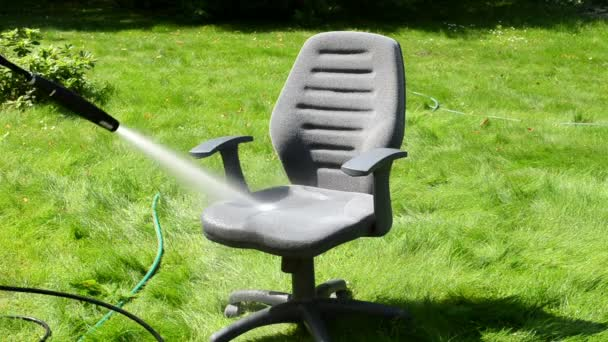 office chair washing under strong stream on green grass