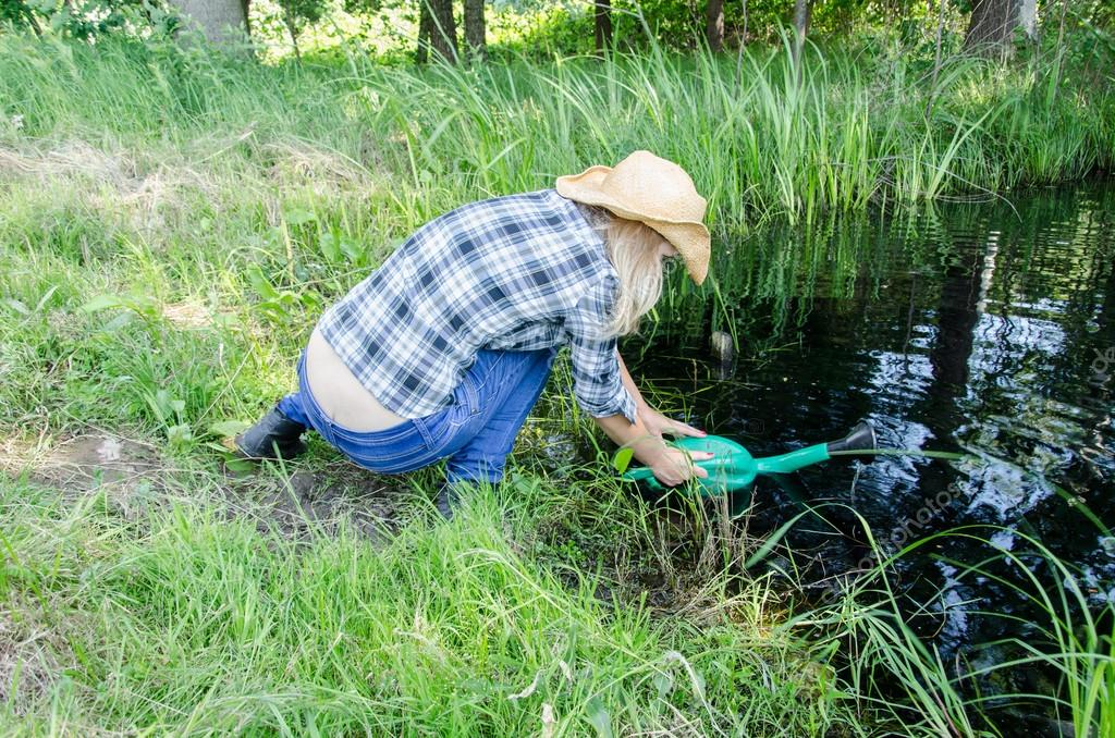 Farm gardener girl draw water from pond