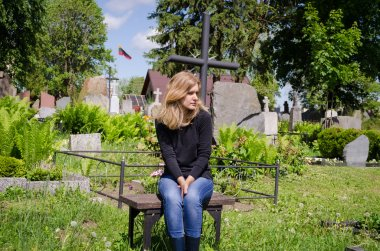Widow woman soldier lover grave. Lithuania flag