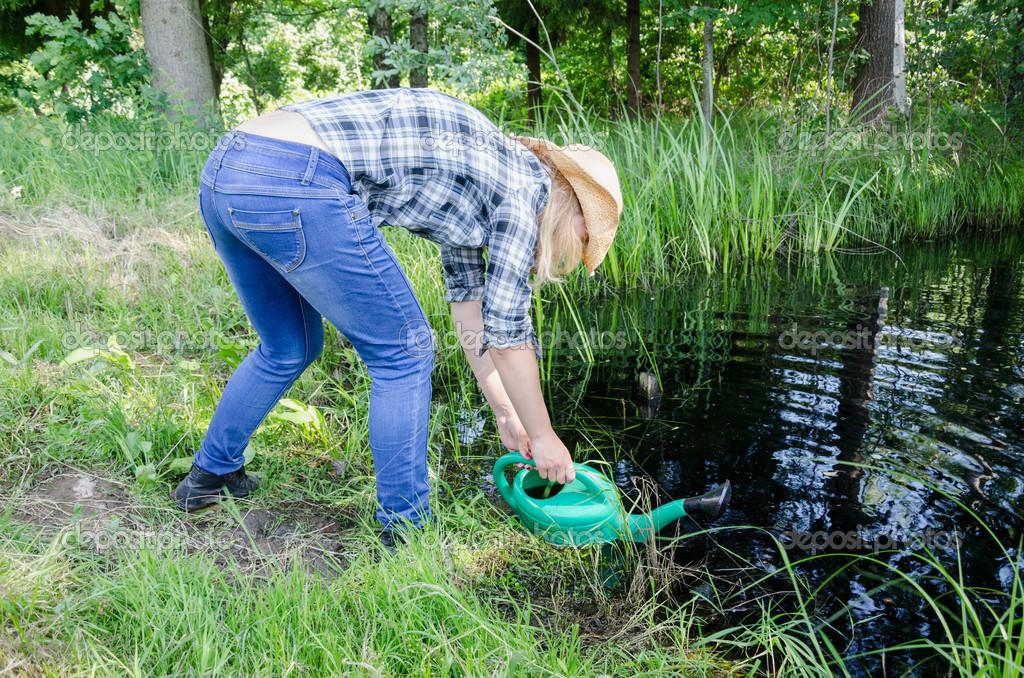 gardener girl draw water from pond