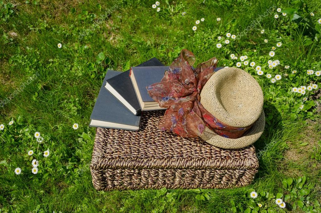 Wicker basket full of books and retro hat on grass