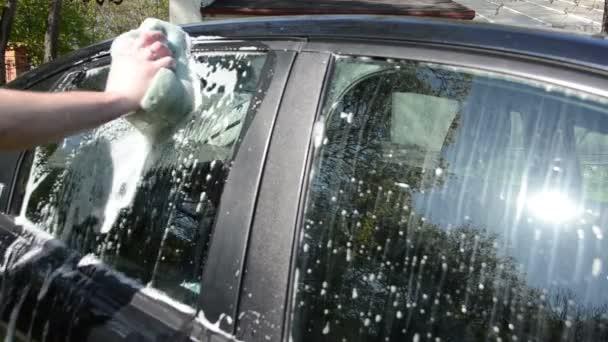 Closeup von Hand mit seifigen Schwamm reinigen waschen Autoglaserei