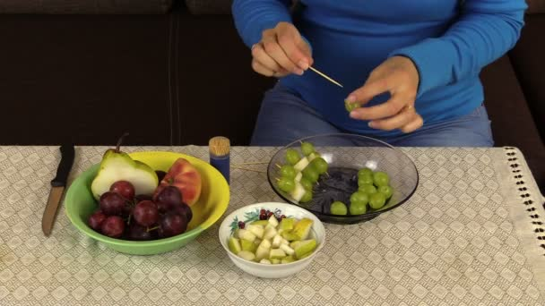 Pregnant woman girl prepare dessert from grapes and fruit pieces