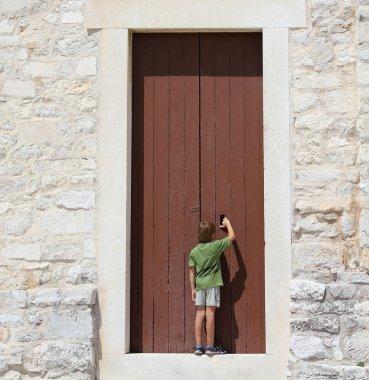 young boy in front of a big door