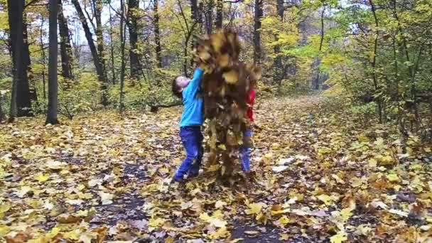 Two kids playing with leafs in the forest