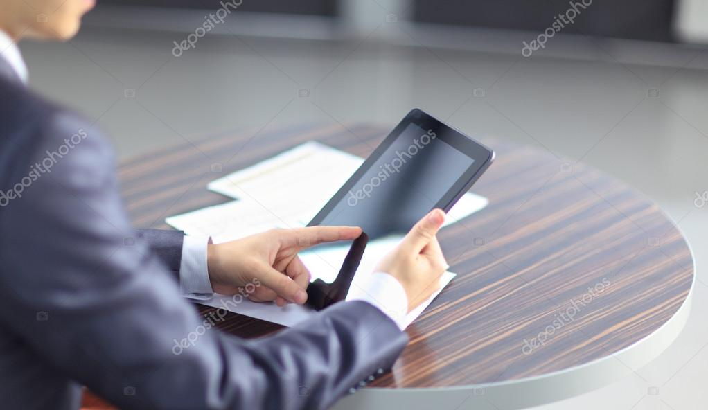 Hand touching on modern digital tablet pc at the workplace.