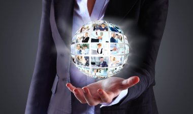 Business woman holding a ball of people on a dark background