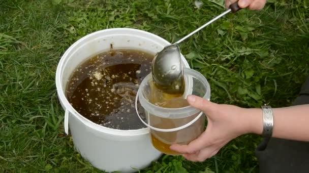 letní med v kbelíku a ruce