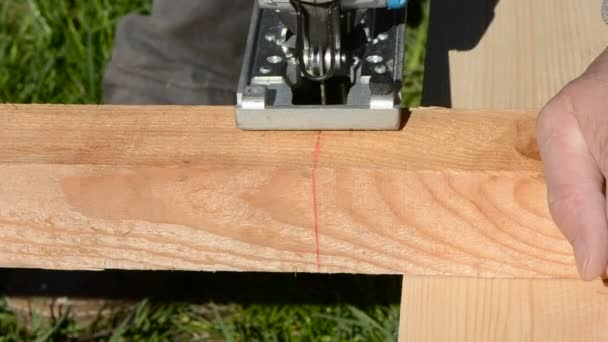 Carpenter with electric saw cut up plank