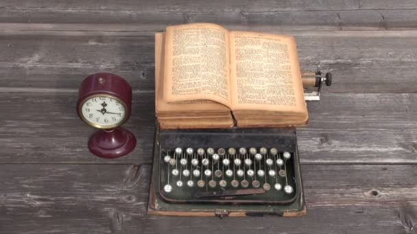 Ancient typewriter and old book on wooden background.